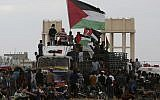 Illustrative: Protesters wave Palestinian flags while riding a truck full with tires near the fence of the Gaza Strip border with Israel during a protest east of Gaza City, Friday, October 26, 2018. (AP/Adel Hana)
