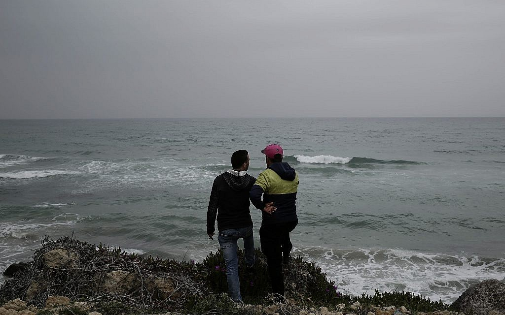 Ahmed Ayouby, 32, left, and Mounir Aguida, 30, who want to leave Tunisia, stand at the beach where migrants leave for Italy, in the town of Ras Jabal, Bizerte, Tunisia, on April 14, 2018. (AP Photo/Nariman El-Mofty)