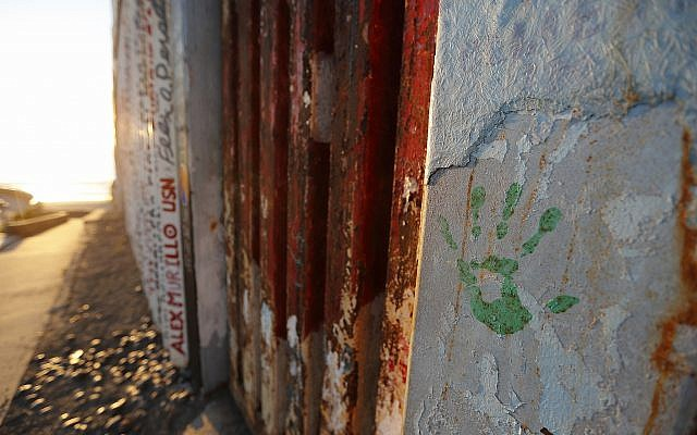 A hand print in honor of migrants that have been killed or are missing is seen on a border wall structure separating Tijuana, Mexico from San Diego, in Tijuana on October 16, 2018. (AP Photo/Gregory Bull)