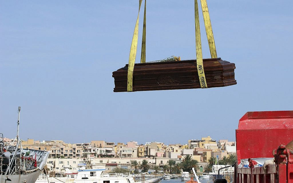 In this October 12, 2013 file photo, the casket of one of the migrants who died when their boat capsized off in the Canal of Sicily is lifted by crane to an Italian Navy ship at the Lampedusa island harbor. (AP Photo/Mauro Buccarello)