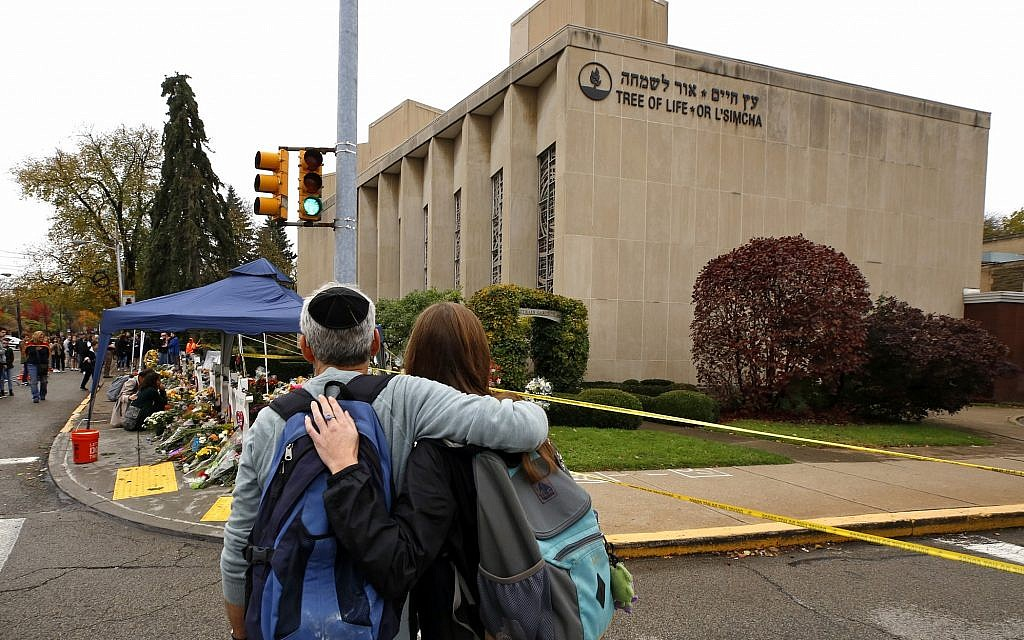 People pay their respects Thursday, November 1, 2018, at a makeshift memorial outside the Tree of Life Synagogue to the 11 people killed October 27, 2018 while worshiping in the Squirrel Hill neighborhood of Pittsburgh. (AP Photo/Gene J. Puskar)