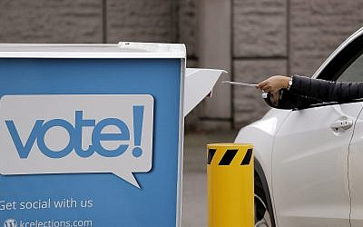 A driver drops a ballot into a drop box at the King County Elections office, November 5, 2018, in Renton, Wash. (Elaine Thompson/AP)