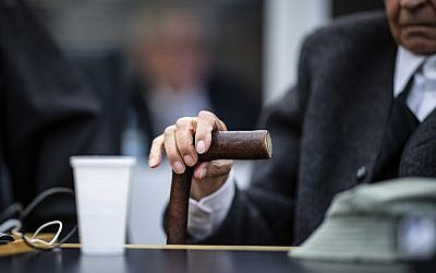 Johann Rehbogen, a 94-year-old former SS guard holds his walking stick at the beginning of a trial in Muenster, Germany, November 6, 2018. (Guido Kirchner/dpa via AP)