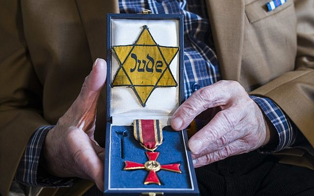 Walter Frankenstein, witness of the November 9, 1938 terror against Jews in Berlin and one of the few survivors of Auerbach'sches Waisenhaus orphanage shows a box with the Yellow badge the Nazis forced him to wear and with the Germany's Federal Cross of Merit he got in 2014, during an interview with the Associated Press in Berlin, November 5, 2018. (Markus Schreiber/AP)