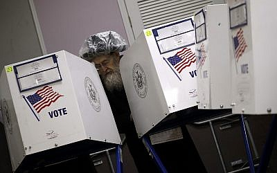 An Orthodox Jewish man fills out his ballot papers at a polling center on Tuesday, Nov. 6, 2018, in Brooklyn borough of New York. (AP Photo/Wong Maye-E)