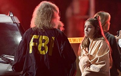 An FBI agent talks to a potential witness as they stand near the scene Thursday, Nov. 8, 2018, in Thousand Oaks, Calif. where a gunman opened fire Wednesday inside a country dance bar crowded with hundreds of people on 'college night' (AP Photo/Mark J. Terrill)