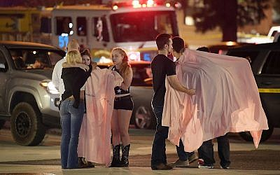 People comfort each other outside the scene of a shooting, November 8, 2018, in Thousand Oaks, California. (AP Photo/Mark J. Terrill)