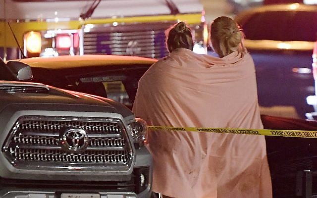 People walk away from the scene Thursday, Nov. 8, 2018, in Thousand Oaks, Calif. where a gunman opened fire Wednesday inside a country dance bar crowded with hundreds of people on 'college night' (AP Photo/Mark J. Terrill)