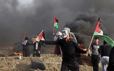 Palestinians wave their national flags while others burn tires near the fence of Gaza Strip border with Israel during clashes east of Gaza City, on November 9, 2018. (AP Photo/Adel Hana)