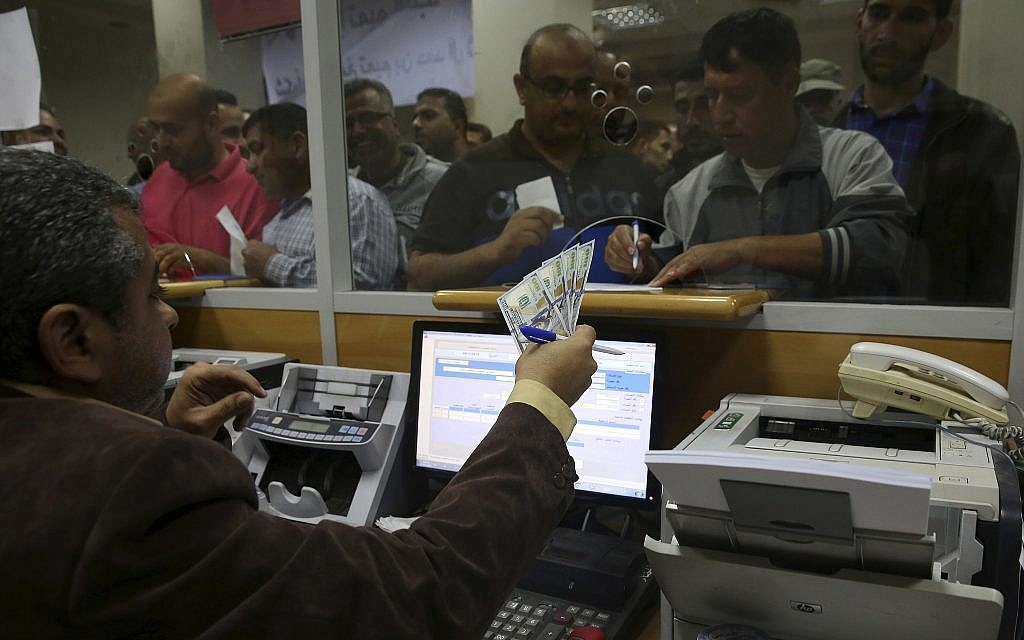 A Palestinian Hamas government employee signs to receive 60 percent of their long-overdue salary while others wait in the queue, at the main Gaza Post Office, in Gaza City, Friday, November 9, 2018. (AP/Adel Hana)