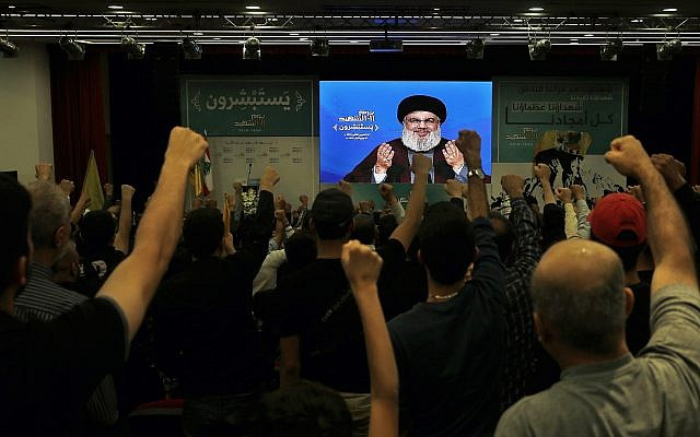 Supporters of the Hezbollah terror group raise their fists and cheer as they listen to a speech by Hezbollah leader Hassan Nasrallah, via a video link, during a rally marking Hezbollah Martyr's Day in Beirut, Lebanon, November 10, 2018. (AP/Bilal Hussein)