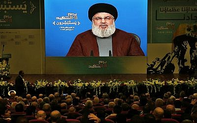 Supporters of the Iranian-backed Hezbollah terror group listen to a speech by leader Hassan Nasrallah, via a video link, during a rally marking Hezbollah Martyr's Day, in a southern suburb of Beirut, Lebanon, November 10, 2018. (AP Photo/Bilal Hussein)