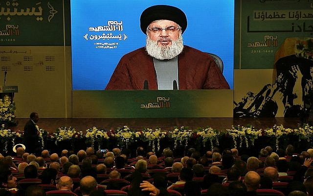 Supporter of the Iranian-backed Hezbollah terror group listen to a speech by Hezbollah leader Hassan Nasrallah, via a video link, during a rally marking Hezbollah Martyr's Day, in a southern suburb of Beirut, Lebanon, Nov. 10, 2018. (AP Photo/Bilal Hussein)