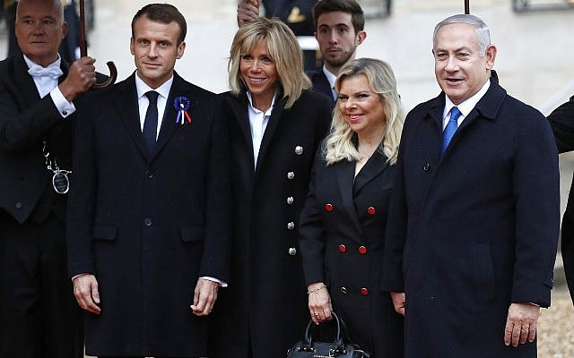 Prime Minister Benjamin Netanyahu, right, and his wife Sara, second right, are greeted by French President Emmanuel Macron, left, and his wife Brigitte Macron as they arrive at the Elysee Palace in Paris to participate in a World War I Commemoration Ceremony, November 11, 2018 (AP Photo/Christophe Ena)