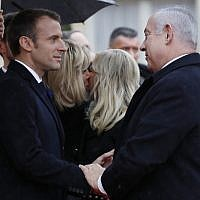 French President Emmanuel Macron, left, welcomes Israeli Prime Minister Benjamin Netanyahu, right, while and his wife Sara kisses Brigitte Macron, second left, in the courtyard of the Elysee Palace Sunday, Nov. 11, 2018 in Paris.  (AP Photo/Thibault Camus)