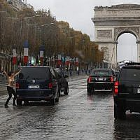 French police officers run after a topless protester who rushes the motorcade of US President Donald Trump on the Champs Elysees in Paris, November 11, 2018 (AP Photo/Jacquelyn Martin)