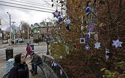 In this Tuesday, Nov. 20, 2018 photo, Stars of David hang from bushes outside the post office in the Squirrel Hill neighborhood of Pittsburgh. (AP/Gene J. Puskar)