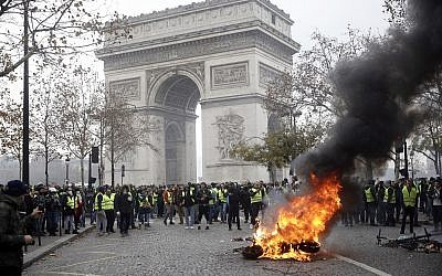Demonstrators, called the yellow jackets, gather around the Arc de Triomphe as they protest against the fuel taxes, in Paris, France, Nov. 24, 2018 (AP Photo/Kamil Zihnioglu)