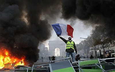 A demonstrator waves the French flag onto a burning barricade on the Champs-Elysees avenue with the Arc de Triomphe in background, during a demonstration against the rising of the fuel taxes, Saturday, Nov. 24, 2018 in Paris. (AP/Michel Euler)