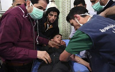 This photo released by the Syrian official news agency SANA, shows medical staff treating a boy following a suspected chemical attack on his town of al-Khalidiya, in Aleppo, Syria, Nov. 24, 2018 (SANA via AP)