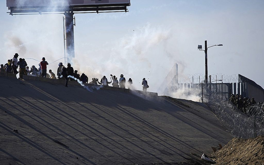 Migrants in Mexico stand amid tear gas launched by US agents at the border with the US, right of fence, after a group of migrants pushed past Mexican police at the Chaparral crossing in Tijuana, Mexico, Nov. 25, 2018 (AP Photo/Ramon Espinosa)