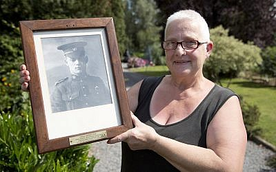 Resident Marilyn Lahaeu holds up a photo of World War I soldier Pvt. George Lawrence Price, who was killed in the Belgian village of Ville-sur-Haine, in 1918, near her home in Ville-sur-Haine, Belgium, Sunday, Aug. 3, 2014. (AP Photo/Virginia Mayo)
