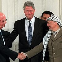 President Clinton gestures toward Israeli Prime Minister Yitzhak Rabin, left, and PLO leader Yasser Arafat shaking hands in the East Room of the White House Thursday Sept. 28, 1995. Egyptian President Hosni Mubarak looks on behind Arafat. (AP Photo/Doug Mills)