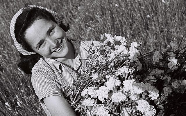 A girl with a bunch of carnations in a field at moshav Mishmar Hasharon (GPO, Public Domain/Wikimedia Commons)