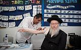 Deputy Health Minister Yaakov Litzman gets his flu shot at the Efrata Elementary School in Jerusalem on October 26, 2017. (Hadas Parush/Flash90)