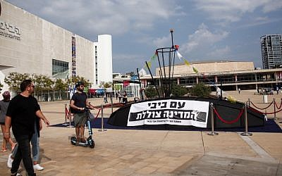 Israelis look at a submarine-like structure with a sign reading 'With Bibi [Netanyahu], the country is sinking,' at Habima Square in Tel Aviv, November 10, 2018. (Miriam Alster/Flash90)