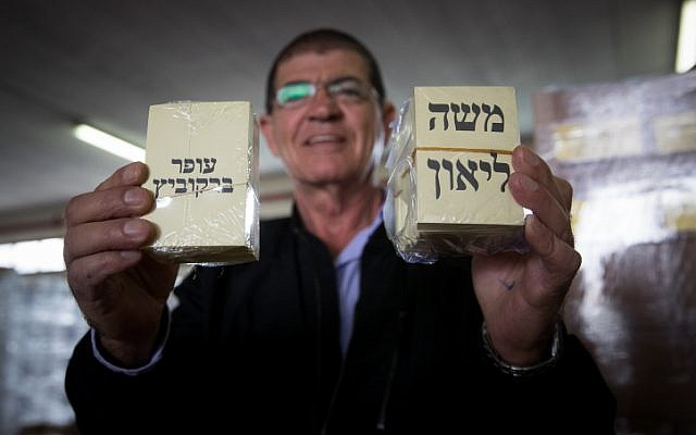 A man holds voting notes of Jerusalem mayoral candidates Ofer Berkovich and Moshe Lion, during preparations for the upcoming second round of the Jerusalem municipal elections, at a warehouse in Jerusalem on November 11, 2018. (Yonatan Sindel/Flash90)