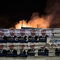 Local elections campaign posters can be seen as smoke rises behind from a building that was set ablaze by a rocket fired from the Gaza Strip, in the southern Israeli city of Sderot on November 12, 2018. (Hadas Parush/Flash90)