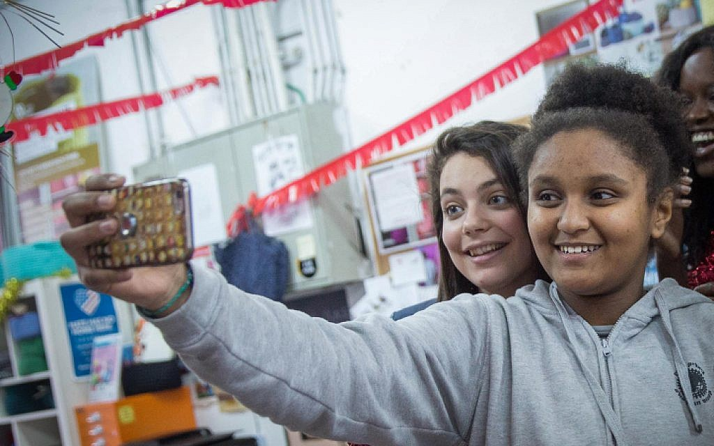 12-year old Sylvana Tsegai, right, taking a selfie at a Christmas party organized by the Kuchinate collective, in south Tel Aviv, January 9, 2018. (Miriam Alster/Flash90)