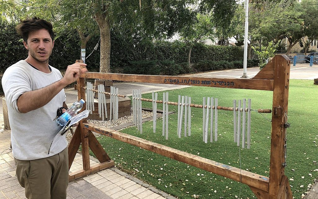 The oversized xylophone that was made and placed in a public space by Matan Saad, pictured here, along with other members of Beersheva's placemaking volunteers, and then broadened into a playground by the city, as part of the efforts to change the look and feel of the southern city (Jessica Steinberg/Times of Israel)