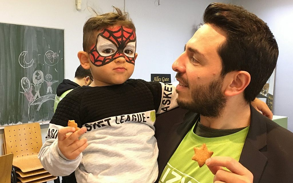 Dervis Hizarci, of the Kreuzberg Initiative Against Antisemitism, with his three-year-old son, at Mitzvah Day at the Dueppel Youth Center in Berlin, November 18, 2018. (Toby Axelrod/ Times of Israel)