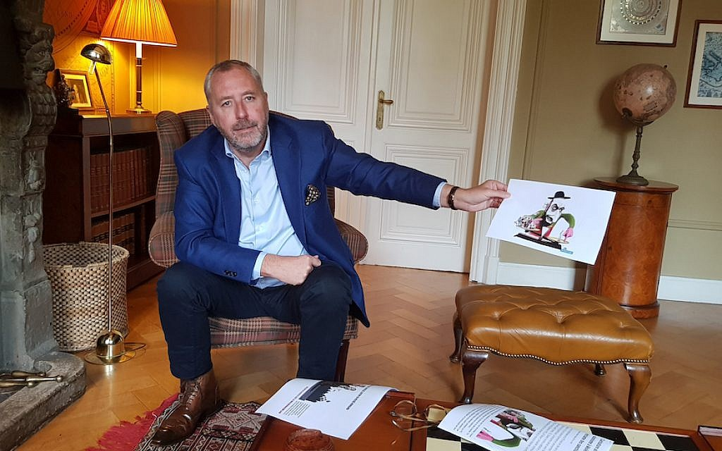 Mischael Modrikamen at his home near Brussels holds up an anti-Semitic caricature favored by anti-Israel circles in Belgium, Oct. 26, 2018. (Cnaan Liphshiz)