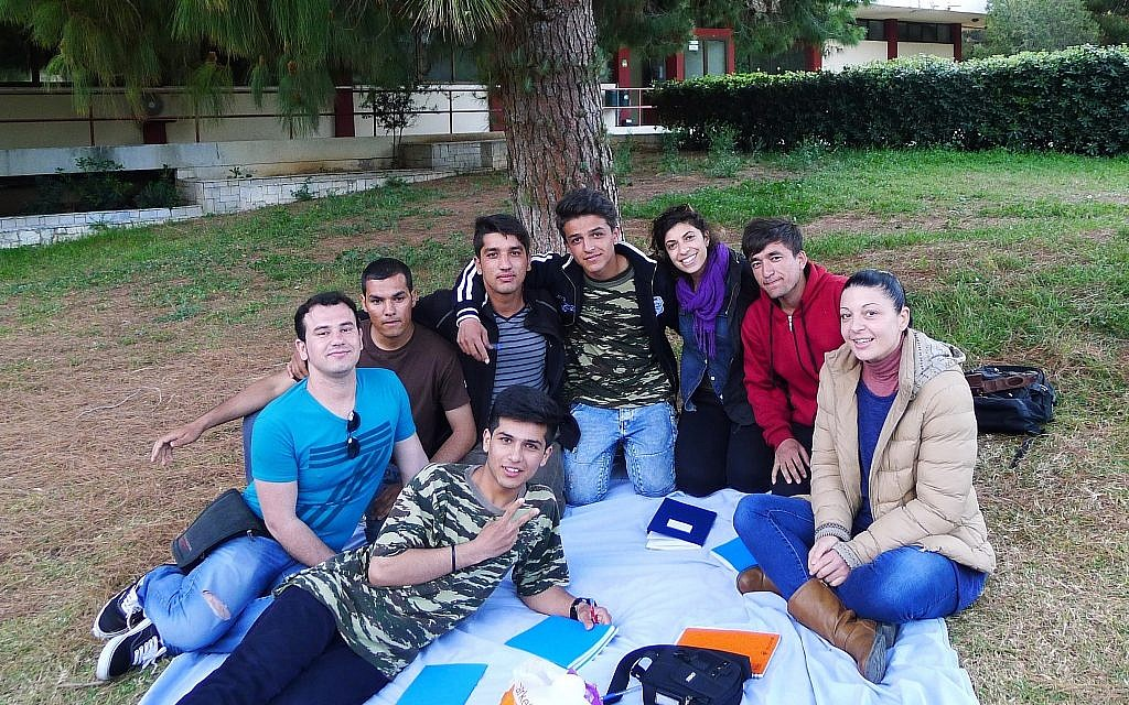 Hadas Yanay, center, outside the Elliniko refugee camp in Greece with her young Afghan language exchange students. (Courtesy)