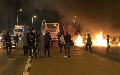 Residents of Israeli communities near the Gaza Strip burn tires and block a road at the entrance to the city of Sderot in protest of a ceasefire agreement, November 14, 2018. (Israel Police)
