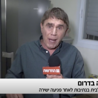 Hadashot TV reporter Moshe Nussbaum in a home in Netivot hit by a piece of shrapnel from a Hamas-fired rocket, November 12, 2018 (Hadashot TV news)