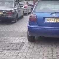 A screen capture from video footage reportedly filmed in Amman, Jordan, shows cars with Israeli license plates being used in the production of a Netflix project based in Tel Aviv. (Screen capture: YouTube)