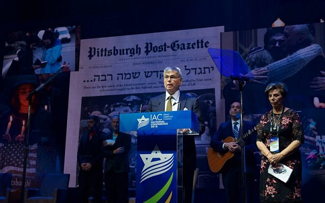 Rabbi Alvin Berkun, rabbi emeritus of The Tree of Life/Ohr Kodesh congregation in Pittsburgh, and Tzippy Holland, a Holocaust survivor, join at the Israeli American Council conference in a tribute to the police who stopped the massacre at a Pittsburgh synagogue, Nov. 29 2018. (IAC via JTA)