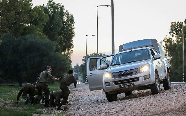 Israeli soldiers lying on the side of the road in southern Israel as they take cover from incoming rockets fired from Gaza into Israel, November 12, 2018. (Hadas Parush/Flash90)