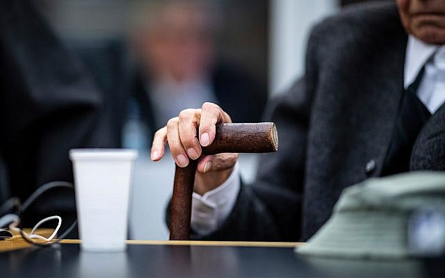 A 94-year-old former SS guard holds his walking stick at the beginning of a trial in Muenster, Germany, November 6, 2018. He is charged with accessory to murder for serving at the Nazis' Stutthof concentration camp. (Guido Kirchner/dpa via AP)