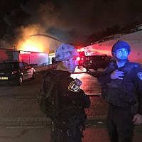 Police officers stand next to a building fire in Sderot on November 12, 2018. (Israel Police)