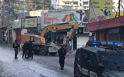 Police accompany bulldozers demolishing storefronts in the Shuafat Refugee Camp in East Jerusalem, November 21, 2018. (Courtesy Ir Amim)