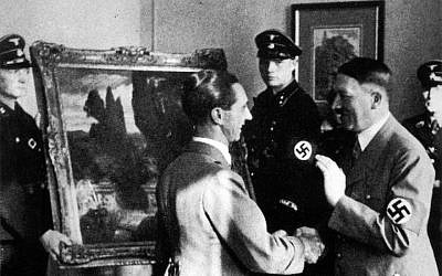 Illustrative: Adolf Hitler, right, looking at a stolen artwork in 1940. (Photo12/UIG via Getty Images)