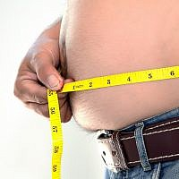 Illustrative image of obesity, with a man measuring his belly sanchairat; (iStock by Getty Images)