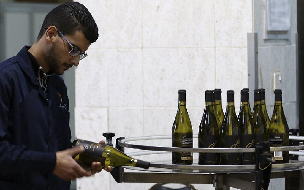A picture taken on October 31, 2018, shows workers inspecting the bottles inside Eagle Distilleries in Zarqa, Jordan, 30 kilometers east of Amman. (Khalil Mazraawi/AFP)
