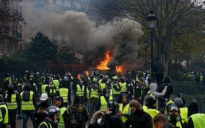 Demonstrators gather in front of a burning car during a protest of Yellow vests (Gilets jaunes) against rising oil prices and living costs, on December 1, 2018 in Paris. (Geoffroy VAN DER HASSELT / AFP)