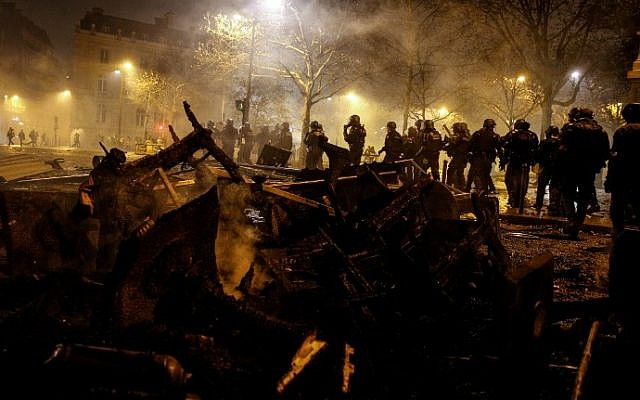 Riot police walk past burnt chairs and tables, during a protest of Yellow vests (Gilets jaunes) against rising oil prices and living costs, on the Champs Elysees avenue in Paris on December 1, 2018 (Photo by Geoffroy VAN DER HASSELT / AFP)